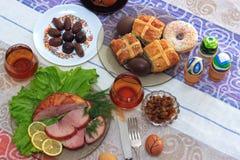 Tradycyjny Easter obiadowy ustawiający z pokrojonym mięsem z cytryną, ziele, handmade barwioni jajka, czekolady, rodzynki, Easter Obrazy Stock
