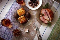Tradycyjny Easter obiadowy ustawiający z pokrojonym mięsem z ziele, czekoladowymi jajkami, Easter tortem i szkłami, sok i świeczk Obraz Royalty Free