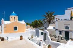 Tradycyjny Grecki jard z biel domami i małym kościół na tle przy Oia miasteczkiem, Santorii wyspa, Grecja zdjęcie stock
