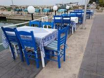 Tradycyjny grecki tawerny błękit zgłasza i krzesła obraz stock