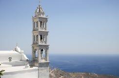 Tradycyjny greckiego kościół dzwonkowy wierza i morze egejskie w Tinos, Grecja Zdjęcia Stock