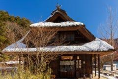 Tradycyjny japończyk pokrywający strzechą dachu dom w Sato Nenba tradycyjnej wiosce zakrywającej śniegiem w Saiko jeziornym teren zdjęcia royalty free