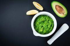 Tradycyjny meksykański kumberlandu guacamole w ceramicznym białym pucharu, cytryny i cięcia przyrodnim avocado na ciemnym tle, Zdjęcie Royalty Free