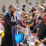 Tradycyjny ortodoksyjny paschalny rytuał - ksiądz błogosławi Easter jajko Zdjęcia Stock