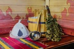 Tradycyjny rosjanina skąpania wyposażenie na drewnianej ławce Drewniany wiadro, kopyść, dębowa miotła, kąpielowy kapelusz i ręczn Zdjęcia Royalty Free