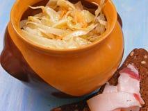 Tradycyjny rosyjski kuchni Sauerkraut w ceramicznym lufowym garnku z przerwą i okrasą na błękitnym podławym tła zakończeniu up fotografia royalty free