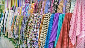 Tradycyjny tkanina sklep z stertami kolorowe tkaniny, tkanin rolki przy rynku kramem - przemysłu włókienniczego tło z zamazanym Zdjęcia Stock