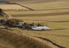 Tradycyjny uprawiać ziemię w Iceland Białe round bele z trawy lying on the beach blisko gospodarstwa rolnego na suchej żółtej tra obraz royalty free