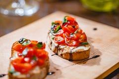 Tradycyjny Włoski bruschetta z czereśniowymi pomidorami, serem, basilem i balsamic octem na drewnianej desce, zdjęcia royalty free