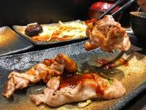 Tradycyjny, wieprzowina plasterek na czarnych chopsticks zdjęcia royalty free