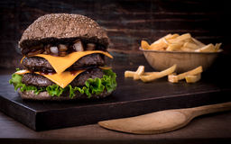Tradycyjny wołowina hamburger z sałatką, karmelizującą cebulą i pomidorem na górze, drewnianej deski wieśniaka tła i Zdjęcia Stock
