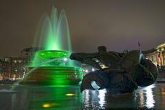 Trafalgar广场在伦敦,喷泉在晚上 免版税库存图片
