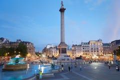 Trafalgar fyrkant med folk i en klar afton i London Arkivfoto