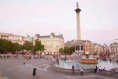 Trafalgar fyrkant med folk och turister på skymning i London Royaltyfria Bilder