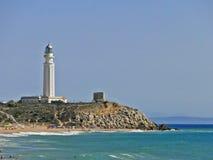 Trafalgar lighthouse with people on the beach. People bathe near the lighthouse with great waves Stock Photo