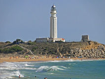 Trafalgar lighthouse with people on the beach. People bathe near the lighthouse with great waves Royalty Free Stock Photo