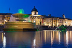 The National Gallery and Trafalgar Square, London. Trafalgar Square in the evening, the National Gallery. In the foreground - illuminated fountain and pool Stock Image