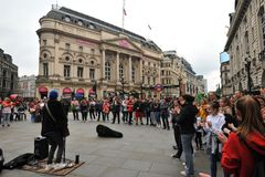 Musician in Trafalgar Square and tourists , London , England stock photography