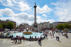 Trafalgar square in a sunny day with people in London. Trafalgar square in a sunny day, people and tourists on August 10th, 2015 in London, UK. The square name royalty free stock photo