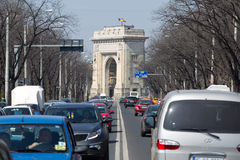 Traffic. On the boulevard Constantin Prezan from Bucharest and the Arc de Triomphe in the plane away.Romania Stock Images