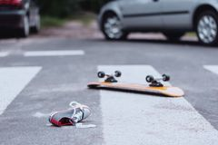 Traffic accident at pedestrian crossing. Teenager`s shoe and skateboard lying on a pedestrian crossing after traffic accident royalty free stock images