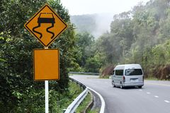 Traffic alerts sign and car driving. Curve road royalty free stock photography