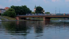 Traffic along Grunwald bridge, Krakow, Poland. The view on Grunwald Bridge across Vistula river with fast riding trams and the bell towers of St Michael the stock footage