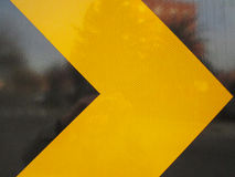 Traffic arrow. Close up of yellow on black reflective traffic arrow Stock Photos