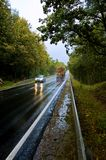 Traffic on autumn road. Fast moving timber truck and car on wet asphalt road through the woods Stock Image