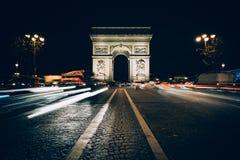 Traffic on Avenue des Champs-Élysées and the Arc de Triomphe a. Traffic on Avenue des Champs-Élysées and the Arc de Triomphe at night in Paris Stock Photo