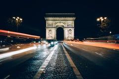 Traffic on Avenue des Champs-Élysées and the Arc de Triomphe a. Traffic on Avenue des Champs-Élysées and the Arc de Triomphe at night in Paris Stock Images