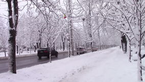 Traffic on a boulevard in winter. Traffic resumed on a city boulevard with cars on lanes after heavy snowfall in wintertime stock video footage