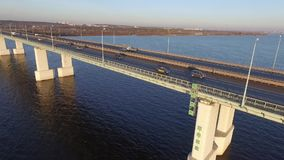 Traffic on the bridge on the Kama River. Autumn, aerial, sunset. Big bridge on the Kama River in the city of Perm. Autumn. Span of the bridge stock footage