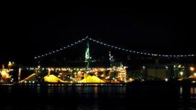 Traffic On Bridge Near Industrial Plant. Night scene of suspension bridge over bay near industrial  facility stock footage
