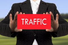 Traffic. Businesswoman in a black jacket shows a card with the inscription traffic. Selective focus Royalty Free Stock Photos