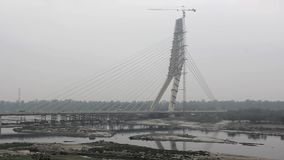 Traffic on the cable-stayed bridge under construction over the Yamuna river in cloudy weather. Signature Bridge. Delhi India. A traffic on the cable-stayed stock video footage