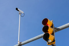 Traffic Camera Next To Traffic Light. Image of a traffic camera mounted next to and above a traffic light which has just turned red stock images