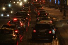 Car traffic on a winter night during a snowfall. Traffic of cars on a winter night during a blizzard Stock Images