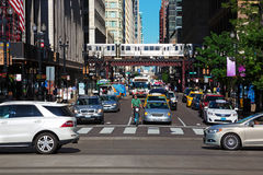 Traffic in Chicago downtown. Chicago, Illinois, USA - June 2016: Traffic at a crossroad in downtown, while in the back a train transits on elevated railway Stock Photo