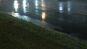 Traffic in the city at rainy night. Night view of car traffic on the wet road with puddles stock video footage
