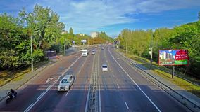 Traffic on city road. KIEV, UKRAINE - SEPTEMBER 18, 2017: The traffic on Oleny Telihu street, stretching down the hill with lush forest on the roadside, on stock video footage