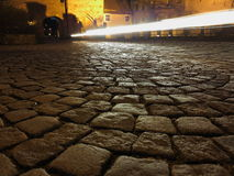 Traffic on cobblestone road at night Stock Image