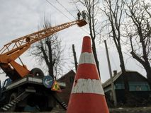 Traffic cone, close-up, on the background of bucket truck with workers. Two men with a chainsaw, standing on the aerial device on. Top, sawing tall trees among stock photos