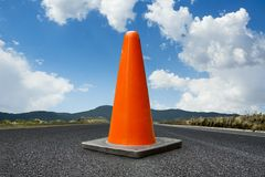 Traffic cone on a road with a bright blue sky Royalty Free Stock Photo