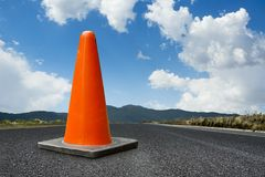 Traffic cone on a road with a bright blue sky. Traffic cone on a road, copy space Stock Image