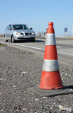 Traffic cone on road with car. Single traffic cone on road with motor car in background Royalty Free Stock Photo
