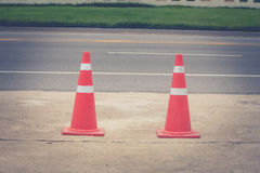 Traffic cone standing on concrete floor at car park beside street. Royalty Free Stock Images