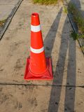 The traffic cone, with white and orange stripes on gray asphalt, copy space Stock Photography