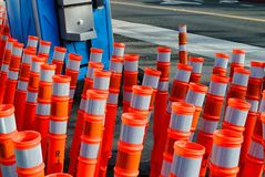 Traffic cones and a porta potty are the essentials for doing roadwork. Bright orange detour cones juxtaposed with a blue portable toilet on the edge of a road royalty free stock image