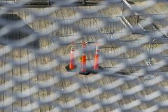 Traffic cones on a slated wooden floor, seen through a white metal grid stock photo